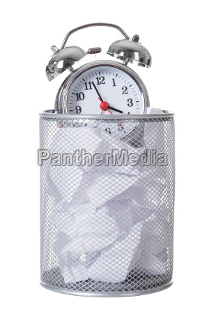 alarm clock on papers in dustbin