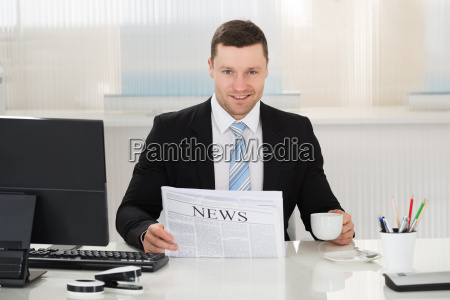 businessman holding newspaper and coffee cup