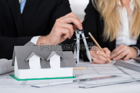 architects working on blueprint with house