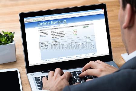 businessman doing online banking on laptop