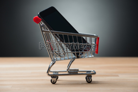 smartphone in shopping cart on table