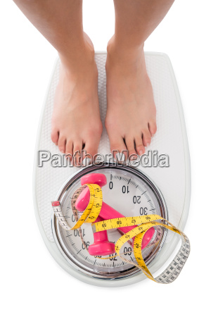 woman stepping on weight scale with