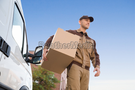 delivery man carrying cardboard box against