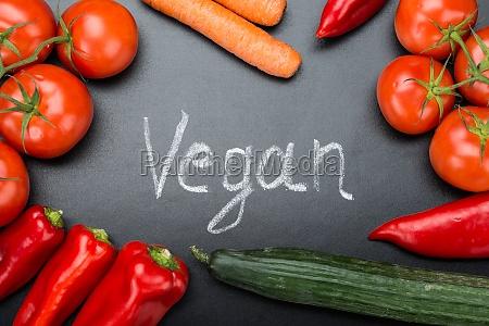 vegan written amidst fresh vegetables on