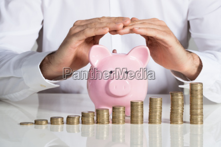 businessman protecting piggybank with stacked coins