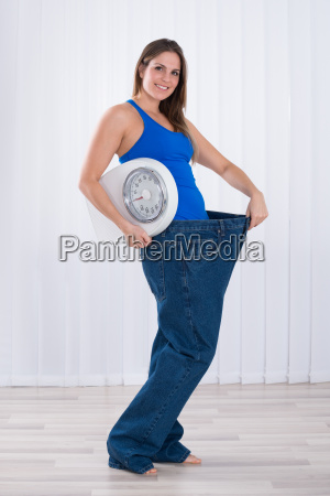 woman with weighing machine wearing big