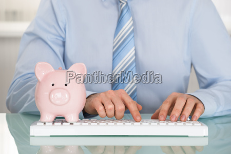 businessman with piggyback and keyboard