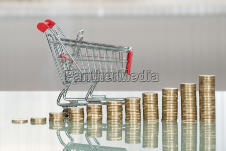 shopping cart and stacked coins on