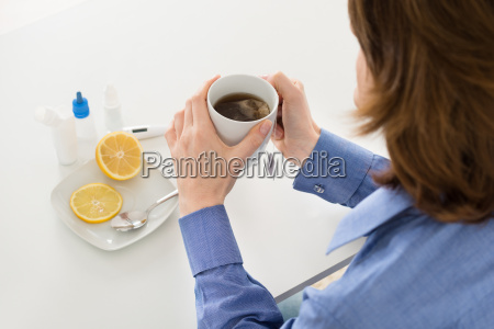 sick woman holding cup of tea