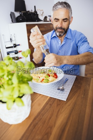 man flavouring his pasta with pepper
