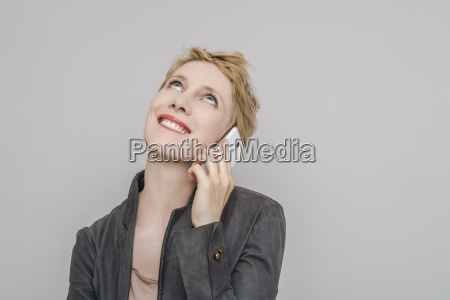 portrait of smiling blond woman telephoning