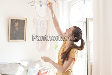 young woman hanging up a top