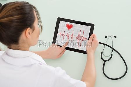 female cardiologist analyzing heartbeat on digital