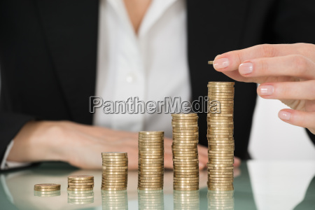 businesswoman placing coin over stack of