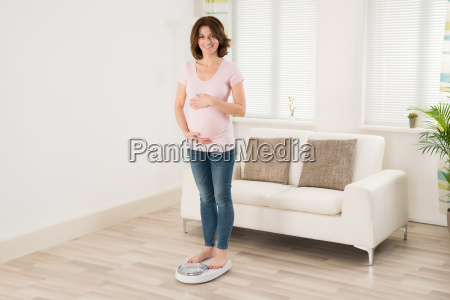 pregnant woman measuring her weight through