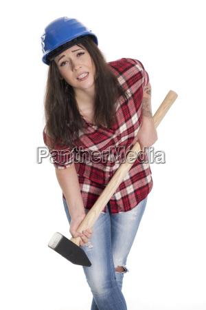 weiblicher handwerker traegt einen schweren vorschlaghammer