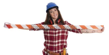 weiblicher handwerker haelt rotes absperrband