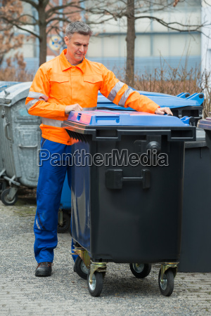 working man standing near dustbin on
