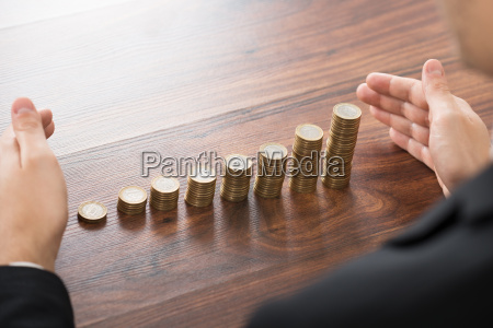 businessman hand protecting stacked coins