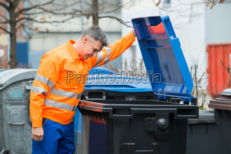 man looking in dustbin on street