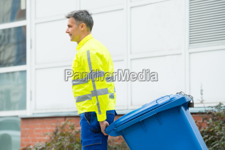 male worker walking with dustbin on