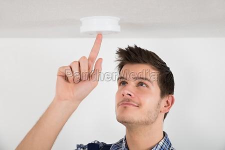 male electrician testing smoke detector