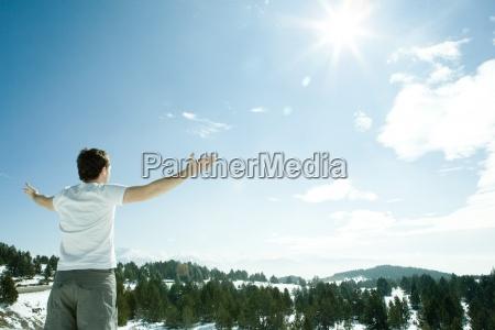 junger mann stehendmit den armen verschneite