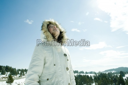 jugendlich maedchen im verschneiten landschaft stehendflachwinkelansicht