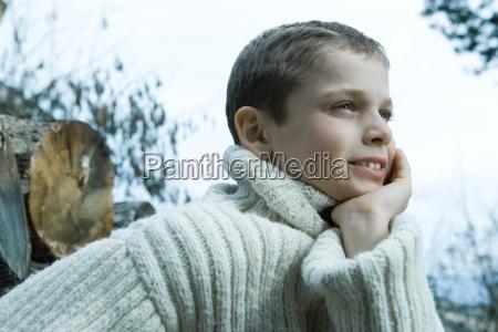 boy tragen wollpulloverhand unter das kinnwegschauen