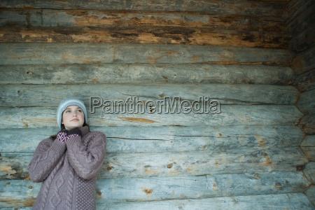 teenie maedchen tragen warme kleidunggelehnt blockhaus