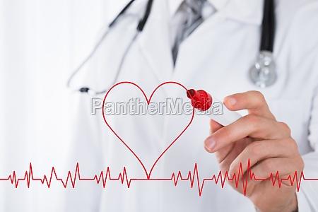 doctor drawing heart symbol near electrocardiogram