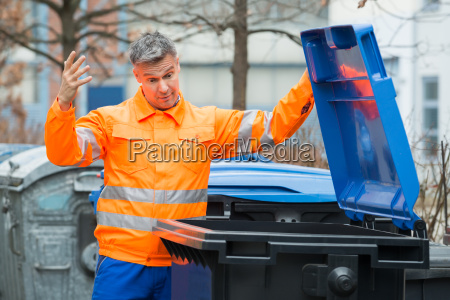 street cleaner looking in dustbin