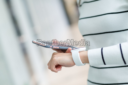 young woman using wearable watch connecting