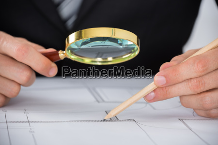 architect hand using magnifying glass on