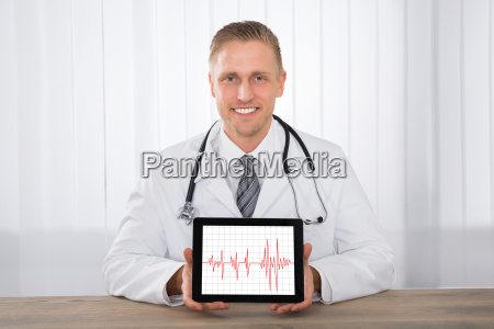 male doctor showing heartbeat on digital