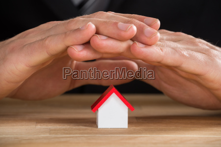businessman hand protecting house model