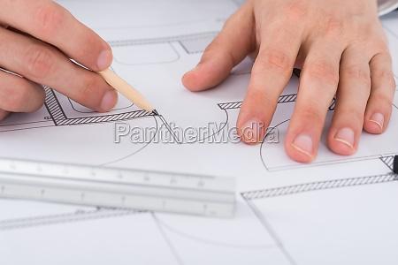 architect hand working on blueprint