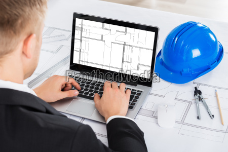 architect analyzing blue print on computer