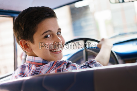 portrait child taking driving lesson in