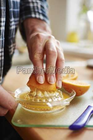 man in pajamas squeezing squeezing orange