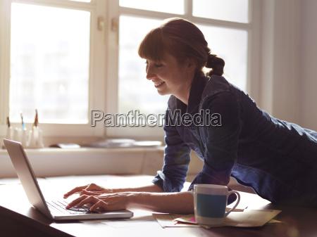 smiling woman at desk using laptop