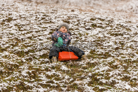 little girl sitting on a sledge