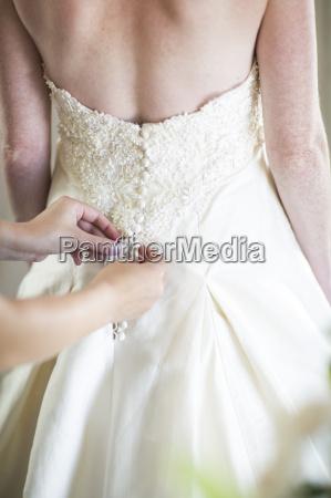 bridesmaid buttoning up brides wedding dress