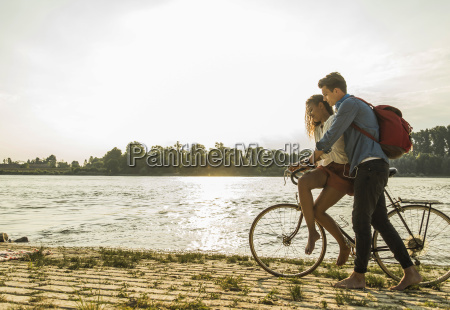 young couple with bicycle by the