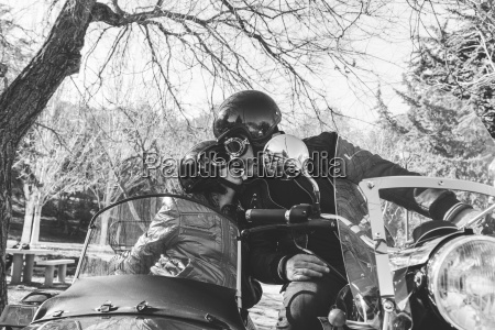 mature couple kissing on sidecar motorbike