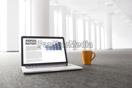 laptop with annual report and cup