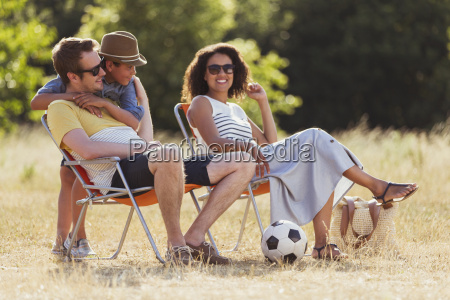 smiling family relaxing in sunny field