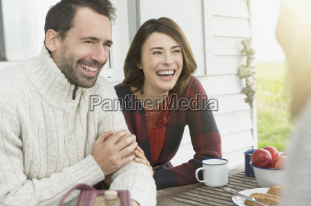 smiling couple talking at table on