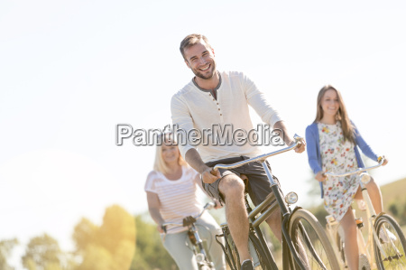 smiling young man bike riding with