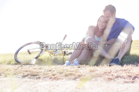 affectionate young couple hugging near bicycle